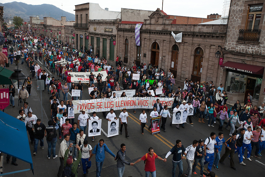 "Parents and relatives of the 43 missing students from Ayotzinapa's teacher training college hold images of the missing students and signs saying ""It was the state"" during a march in Morelia, Michoacan, Mexico on November 19, 2014. The relatives of the 43 missing students still do not believe the official line that the young men are all dead, and with classmates, social organizations and human rights defenders, they started on Thursday a national caravan. They split up into three different caravans, branching out to share information face to face with supporters in other cities and rally nationwide support. The three groups will meet in Mexico City on Thursday 20 for a general strike and massive marches to demand justice and fight against corrupted government and organized crime. Criticism of the government has intensified in Mexico, and many are demanding that the search for the 43 missing students continue until there is concrete evidence to the contrary. (Photo by Bénédicte Desrus)"