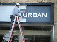 NWA Democrat-Gazette/ANDY SHUPE<br /> Painter Fidel Ventura of Rogers paints over a sign Wednesday, Oct. 9, 2019, above the former Something Urban store at 643 W. Dickson St. in Fayetteville. The store was closed earlier this year by the owner who moved from the area. The location is expected to soon be home to Magnolia Maiden, a clothing boutique based in Prosper, Texas.