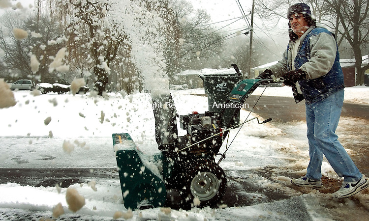 PROSPECT, CT. 19 March 2013-031813S01-Don Snyder of Prospect cleans his driveway during a snowstorm that dumped several inches of snow and ice on the area in Prospect Tuesday..Steven Valenti Republican-American