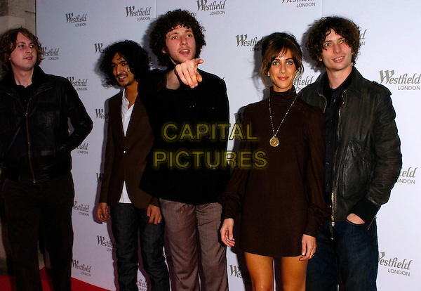 THE ZUTONS - ABI HARDING.Westfield Launch Party for London Fashion Week,.BFC Tent, Natural History Museum, London,.England, September 17th 2006..half length band group brown black polo neck dress gold necklace pendant pointing.Ref: CAN.www.capitalpictures.com.sales@capitalpictures.com.©Can Nguyen/Capital Pictures