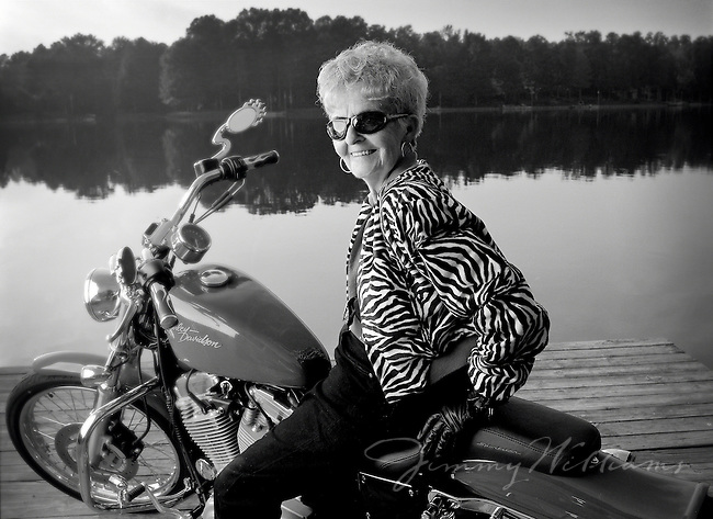 An elderly woman in sunglasses sits on a motorcycle parked at a lakefront.