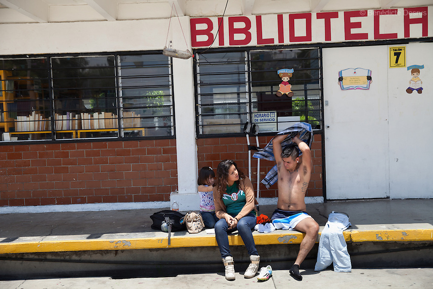 """Rodrigo (R), who is sitting next to his ex-girlfriend and his daughter, gets dressed after a soccer game in Mexico City, Mexico on August 23, 2014. Rodrigo Fernandez Loya, 25,lost his left leg in 2012 when he saved a girl from an onrushing train.Involved in a local 'barrio' gang until his accident, he says that the self-discipline he has developed during his time with Guerreros Aztecas has helped him turn his life around and he is currently studying for his high school diploma. Rodrigo has made the shortlist and is one of the team's biggest hopes to represent Mexico at this December's Amputee Soccer World Cup in Sinaloa. Guerreros Aztecas (""""Aztec Warriors"""") is Mexico City's first amputee football team. Founded in July 2013 by five volunteers, they now have 23 players, seven of them have made the national team's shortlist to represent Mexico at this year's Amputee Soccer World Cup in Sinaloathis December.The team trains twice a week for weekend games with other teams. No prostheses are used, so field players missing a lower extremity can only play using crutches. Those missing an upper extremity play as goalkeepers. The teams play six per side with unlimited substitutions. Each half lasts 25 minutes. The causes of the amputations range from accidents to medical interventions – none of which have stopped the Guerreros Aztecas from continuing to play. The players' age, backgrounds and professions cover the full sweep of Mexican society, and they are united by the will to keep their heads held high in a country where discrimination against the disabled remains widespread.(Photo byBénédicte Desrus)"""