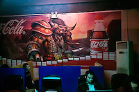 A Coca-Cola soft drink advertisement covers a wall in an internet cafe in Haikou, Hainan, China.