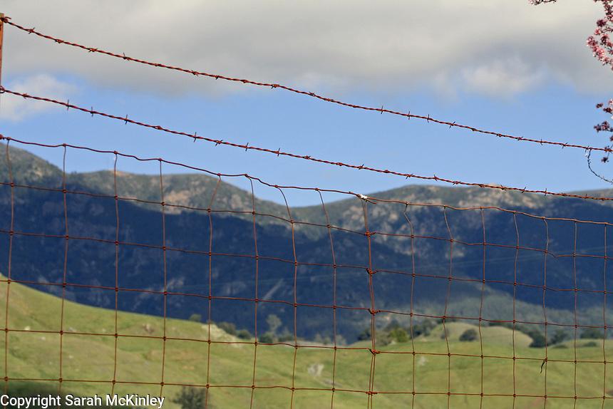 Hills near Geyserville viewed through a rusty wire fence.