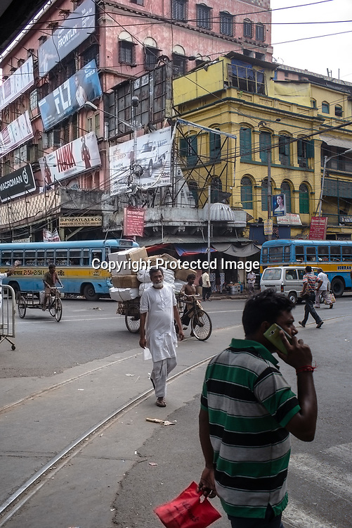 A man speaks on his mobile phone while crossing the junction outside the Mullik Ghat Flower market in Howrah, Kolkata, West Bengal  on Friday, May 26, 2017. Photographer: Sanjit Das