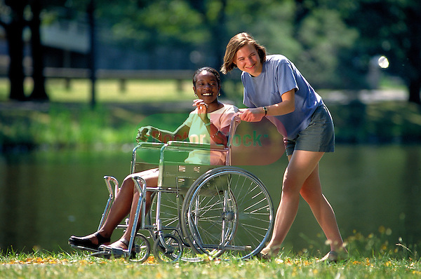 smiling young woman pushing woman in wheelchair in park