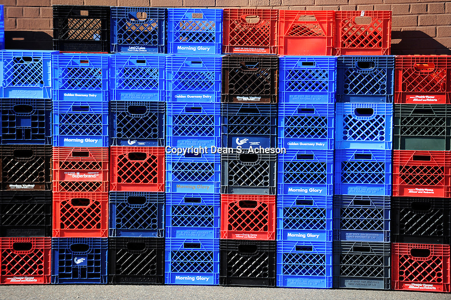 Brightly colored milk crates are stacked in a pattern against a brick wall.