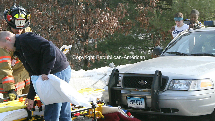 HARWINTON, CT - 7 February, 2009 - 010709MO05 - Ambulance crews prepare to transport the driver of a grey sedan that failed to yeild to a traffic stop and launched his car, with a female passenger, over the guard rail and into the trees off of the Exit 42 off ramp from Route 8 north Saturday. Both occupants were transported to Charlotte Hungerford Hospital for treatment of minor injuries. Jim Moore Republican-American.