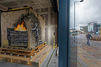 """Pictured: The Banksy at the Ty'r Orsaf building in Port Tabot, Wales, UK. Wednesday 18 December 2019 <br /> Re: A Banksy artwork will be on show to the public for the first time in its new location one year after it was created in Port Talbot, Wales, UK.<br /> The """"Season's Greetings"""" mural appeared on the walls of steelworker Ian Lewis's garage last December.<br /> Gallery owner John Brandler paid a six-figure sum for the work, and agreed that it would stay in the town for three years.<br /> The piece will be on display at the Ty'r Orsaf building.<br /> In May, after months of planning, engineers used a crane to lift the 4.5 tonne mural on to a lorry, before it was escorted by police to its new home.<br /> The Welsh Government funded its transfer amid rising security costs."""