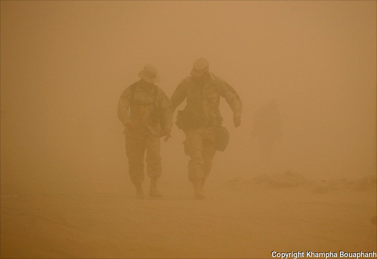 U.S soldiers walk through a sand storm in the Kuwaiti desert on September 12, 2003.  (photo by Khampha Bouaphanh)
