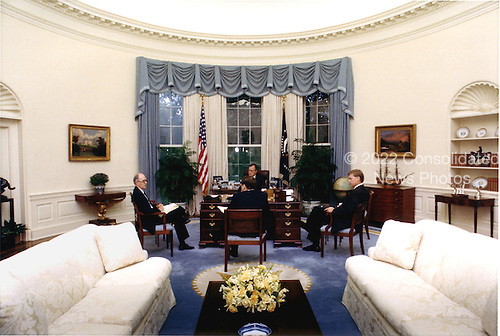 Washington, D.C. - August 9, 1990 -- United States President George W. Bush meets with national security advisors in the Oval Office at the White House in Washington, DC on August 9, 1990 to discuss the situation in the Persian Gulf and Middle East.  National Security Advisor Brent Scowcroft is at far left, President Bush is at center facing camera, Vice President Dan Quayle is at far right, and White House Chief of Staff John Sununu is at center with his back to the camera. .Credit: White House via CNP