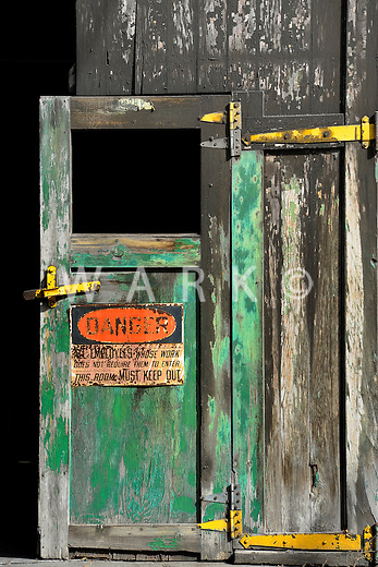 Danger sign on abandoned steel plant door.