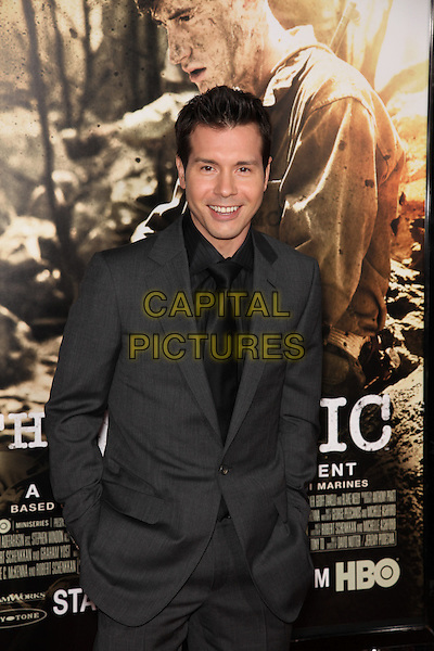 JON SEDA.Arrivals to the Los Angeles Premiere of the HBO Miniseries The Pacific at Grauman's Chinese Theatre, Hollywood, CA, USA, February 24th, 2010. .half length black suit tie shirt grey gray hands in pockets smiling .CAP/CEL.©CelPh/Capital Pictures.