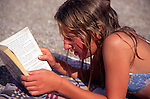 Model released young girl reading book on beach