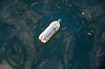 A plastic bottle floats in the oil streaked waters of Baltimore harbor.