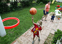 Aleah Pederson, left, adopted daughter of foster parent Bobbi Pederson, shoots a basket as Bobbi chases foster child Kareem Craycraft around the backyard Monday June 16, 2003 in Columbus, Ohio.<br />