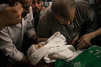 "August 20, 2014 - Gaza City, Gaza strip, Palestinian Territory: Palestinian men carry out the body of the 9-months-old son of Mohammed Al-Daif (not pictured) during his funeral after he was killed during a night raid airstrike in Sheik Redwan neighborhood of Gaza City as ""Protective Edge"" Israeli military operation resumed when the truce was broken in the Gaza strip. (Narciso Contreras/Polaris)"