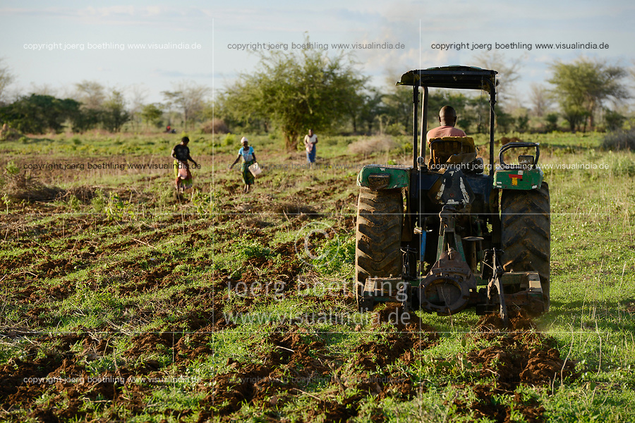 ZAMBIA, Mazabuka, medium scale farmer Stephen Chinyama , he practise conservation farming, ripping furrows with John Deere Tractor to sow cotton seeds, ripping protects the soil instead of ploughing, women sowing cotton