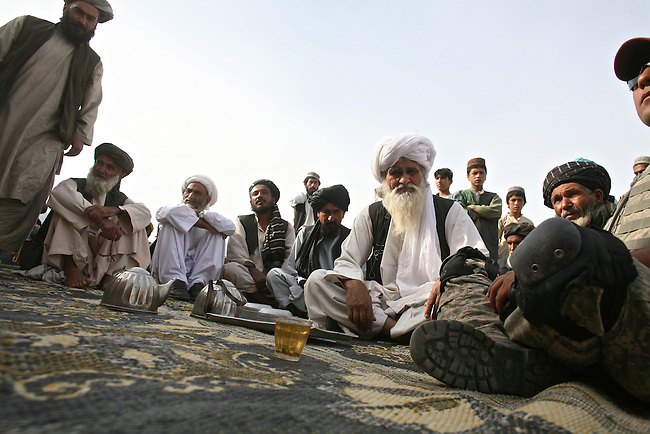 Men in the village of Shuyene Wusa, in the Arghandab valley near Kandahar, Afghanistan meet with U.S. soldiers who have arrived to search the village after a string of bomb attacks on U.S. and Afghan forces nearby. April 10, 2010. DREW BROWN/STARS AND STRIPES