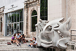 Havana, Cuba; school children sit on the stairs next to the Form, Space and Light sculpture created in 1953 at the entrance to the National Fine Arts Museum