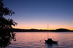 Idaho, North, Coeur d'Alene. A silhouette of a moored sailboat in the summer twilight on Lake Coeur d'Alene.