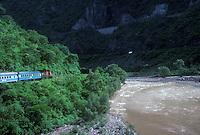 0riginal Ferrocarriles Nacional de Mexico train skirting a river, Copper Canyon, Chihuahua, Mexico. This is an archival image taken in 1990.