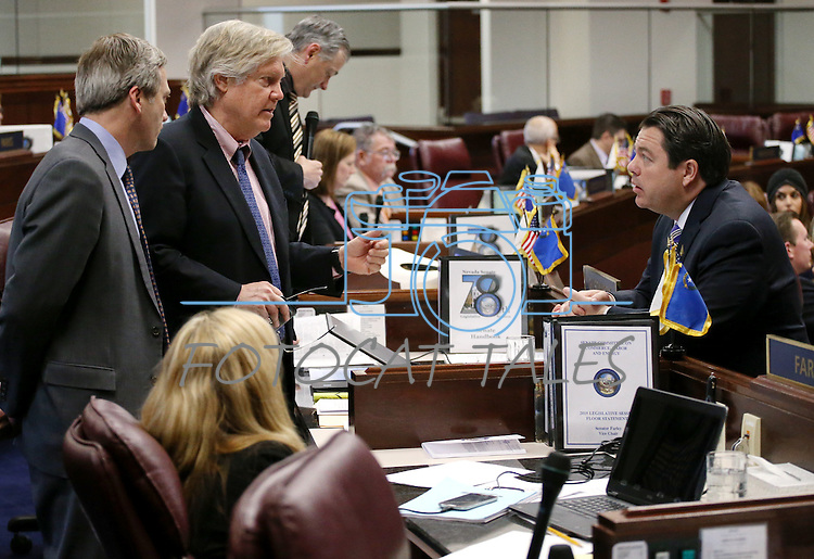 Nevada Sens., from left, Greg Brower, Tick Segerblom and Michael Roberson talk on the Senate floor at the Legislative Building in Carson City, Nev., on Thursday, April 16, 2015.<br /> Photo by Cathleen Allison