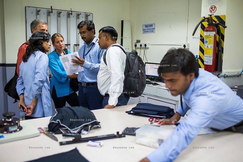 Fairtrade personnel inspect tests being done on textiles in the testing lab at the Pratibha vertically integrated garment unit in Indore, Madhya Pradesh, India on 11 November 2014. Photo by Suzanne Lee for Fairtrade