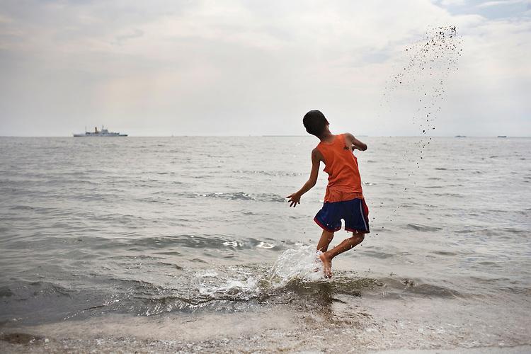 A boy throws sand into the ocean in Manila Bay, Manila, Philippines.