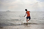 A boy throws sand into the ocean in Manila Bay, Manila, Philippines.