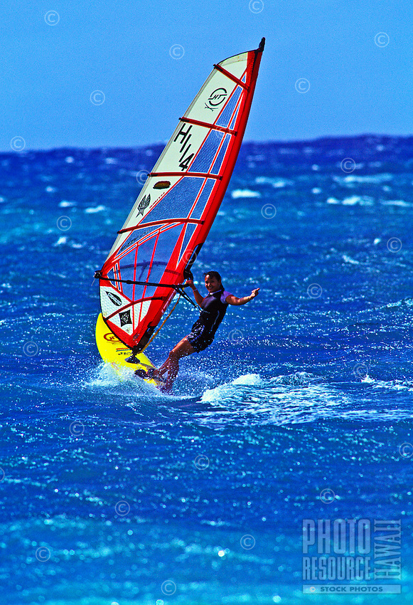 A young woman windsurfer takes a thrilling ride on the clear blue ocean at Kahana Beach Park on the island of Maui.