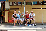 Family day out -  tourists having an ice cream sitting on a bench, Ile des Saintes