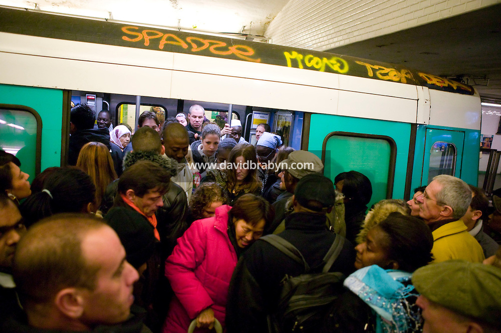People exit and enter a subway train at the Gare Saint Lazare metro station in Paris, France, on day three of a widespread strike by public sector workers which has paralyzed mass transport in the capital. The strike was called to oppose the government's plans to reform the favored retirement plans of 500,000 government employees.