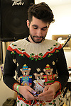 A young man wearing a festive, funny Christmas sweater decorated with three bears dressed for a parade looks down at his mobile phone, at the Jingle Boom Holiday Bash, which has entertainment, and prizes for people wearing the most creative or Ugly Sweaters, at the Main Street Gallery of Huntington Arts Council. Sparkboom, an HAC project, provides events such as this geared to Gen-Y, 18-34 years of age, to address the 'brain drain' of creative young professionals of Long Island. The paintings on the art gallery walls were the Annual Juried Still Life Show.