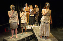 London, UK. 14.01.2013. Nameless Theatre presents THE TROJAN WOMEN, freely adapted from Seneca by Howard Colyer and directed by James Farrell, at the Brockley Jack Studio Theatre. Design by Libby Todd. Lighting design by Steve Lowe. Picture shows: The Chorus (foreground), Jacquie Crago (Hecuba) held by Karl Wilson (Agamemnon - left) and Edward Mitchell (Pyrrhus - right). Photo credit: Jane Hobson.