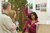 "A current student rattling a string of brazil nuts while showing a father & daughter around the exhibition, ""Heart of Brazil"" by Sue Cunninham. The string of nuts is attached to the ankle whilst dancing.  Open Day at Kingston College when prospective students and their parents look around."