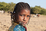 In the season Fulani village of Bantagiri in northern Burkina Faso, reflections of light from the sequins of a young woman's shawl dance across her face.  The Fulani are traditionally nomadic pastoralists, crisscrossing the Sahel season after season in search of fresh water and green pastures for their cattle and other livestock.