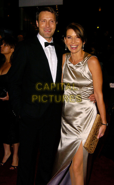 """MADS MIKKELSEN & GUEST.""""Casino Royale"""" World Royal Film Premiere Odeon cinema, Leicester Sqaure, London, UK..November 14th, 2006.Ref: CAN.half length black tuxedo silver grey gray dress satin.www.capitalpictures.com.sales@capitalpictures.com.©Can Nguyen/Capital Pictures"""