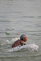 An Indian man taking a holy dip in the polluted dirty water of Ganga in Varanasi, Uttar Pradesh, India.
