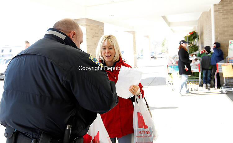 "Southbury, CT- 04, December 2010-120410CM01 Southbury Police Officer, Cpl. Brian Hughes (foreground) receives a donated Christmas gift from Lisa Wheeler, of Southbury Saturday morning outside the K-Mart in Southbury Plaza.  ""Christmas is about giving, not getting presents."", added Wheeler. The Southbury Police Department was outside collecting gifts for the Southbury Needy Fund.  All toys collected will go to children in the community.   Christopher Massa Republican-American"