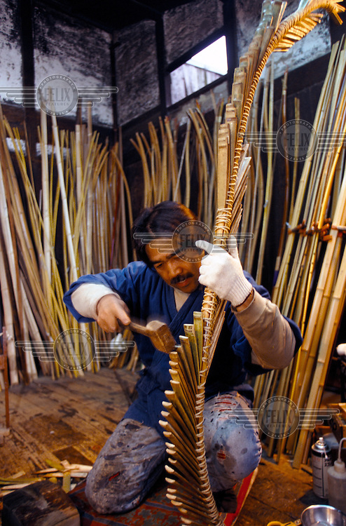 Chibata Kanjuro, a craftsman whose family has been making bows since the 15th century, bends the bamboo frame of a new bow in his workshop.