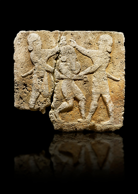 Photo of Hittite relief sculpted orthostat stone panel of Herald's Wall Limestone, Karkamıs, (Kargamıs), Carchemish (Karkemish), 900-700 B.C. Anatolian Civilisations Museum, Ankara, Turkey.<br /> <br /> This relief tells the story the killing of Humbaba, protective deity of the cedar forests, by Gilgamesh and Enkidu. The figures standing on both sides hold, with one hand, the arms of the figure in the middle transversally while they stab the dagger on the head of the figure.  <br /> <br /> Against a black background.