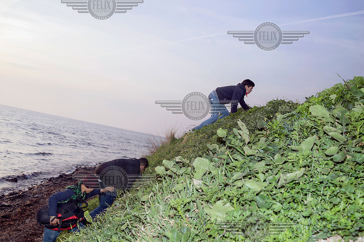 Refugees that have just landed scramble up the hillside to make their way towards the centre of the Island.