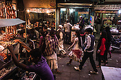 Pedestrians walk past shop vendors waiting for customers at their kebab stall in Nizamuddin, New Delhi, India.