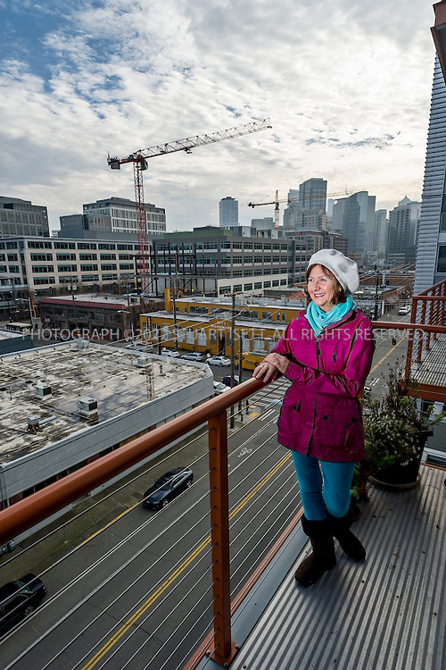 1/22/2013--SEATTLE, WA, USA..Wendy Simons on her balcony overlooking the South Lake Union neighborhood.  Simons moved to SLU from Bellevue, never to look back on her former suburban lifestyle, where making personal connections had been a challenge. ..©2012 Stuart Isett. All rights reserved.