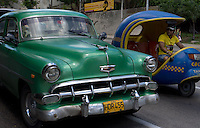 street scene with green oldtimer and coco taxi in Havana, Cuba