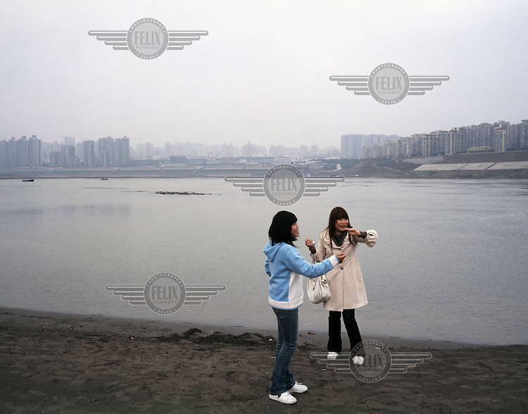 Girls fly kites on the banks of the Yangtze River.
