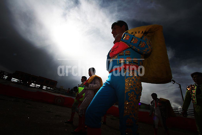 Aymara Indian  bull fighter during  an exhibition in a makeshift  bullring in El Alto, the impoverish city next to La Paz, the capital city of Bolivia. In this kind of sports the objective is not to kill or injure the bull, but to show skills in the fight