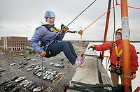 NWA Democrat-Gazette/BEN GOFF @NWABENGOFF<br /> Jene Huffman-Gilreath (from left) of Rogers steps over the edge with guidance from volunteer Cambre Ricker of Fayetteville Saturday, March 11, 2017, during the Sunshine School &amp; Development Center's rappelling fundraiser with Over The Edge at the 8W Center in Bentonville. The school began a campaign in January, with participants who reached their fundraising goal able to participate in rappelling from the roof of the 6-story building. Over the Edge is a company which specializes in producing events for non profits using equipment and techniques used in commercial rope-access work such as sign installation and window washing. The event had raised more than $57,000 for the school, with more donations still coming in Saturday morning. Located in Rogers, the Sunshine School &amp; Development Center serves children and adults with developmental dissabilities, including a preschool.