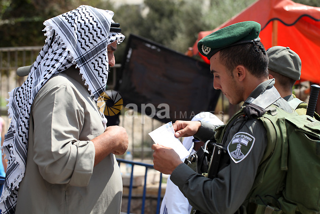 An Israeli policeman checks the documents of a Palestinian muslim as others block Palestinians from praying in the city's Al-Aqsa mosque, in the Ras Al-Amud neighborhood of East Jerusalem on Spe. 26, 2014. Israeli police stepped up security around the mosque, deploying 2,000 troops in Jerusalem and erected roadblocks at entrances to Jerusalem's Old City to prevent possible clashes. Photo by Ameer Abed Rabbo